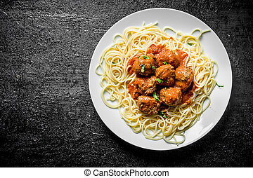 Spaghetti with meat balls on a plate.