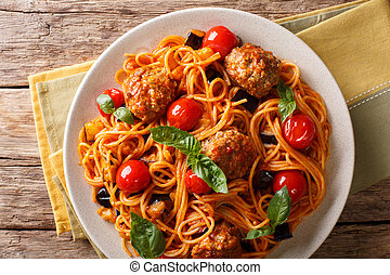 Spaghetti with meat balls, vegetables in a tomato sauce close-up on a plate on a table. horizontal top view, rustic
