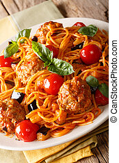 Spaghetti with meat balls, vegetables in a tomato sauce close-up on a plate on a table. vertical, rustic