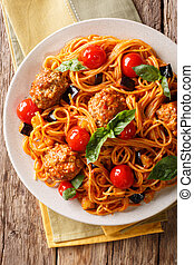 Spaghetti with meat balls, vegetables in a tomato sauce close-up on a plate on a table. Vertical top view, rustic
