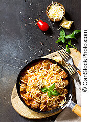 Spaghetti with Meatballs with Tomato Sauce and Parmesan Cheese on a dark stone or concrete background. Top view flat lay background. Copy space.