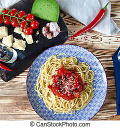 Spaghetti with red sweet pepper and sesame sauce lie on a blue plate on a wooden table