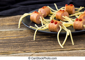 spaghetti with sausages in the form of spiders. Happy kid food for Halloween party. copyspace