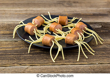 spaghetti with sausages in the form of spiders. Happy kid food for Halloween party