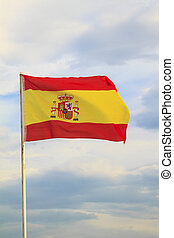 Spain flag on a blue sky with clouds background