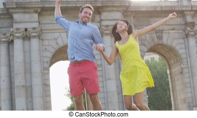 Spain - Madrid Tourists couple jumping cheering by Puerta de...