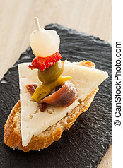 """Spanish appetizer with cheese, anchovy, pepper, olive and onion on a slice of bread called """"Gilda""""."""