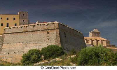 Medium low-angle corner still shot of ancient Spanish brick buildings with upper ventilation openings, Ibiza, Spanish Island, Spain