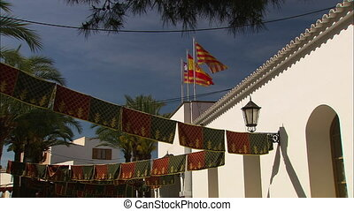 Medium low-angle still shot of the top part of a Spanish building with catolonia flags at the rooftop, hanging symbolic religious prayer clothes, and coastal palm leaves, Ibiza Island, Spain