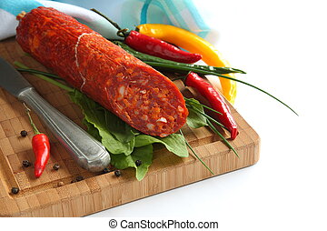 Spanish chorizo sausage with chili peppers on a wooden board