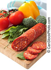 Spanish chorizo sausage with vegetables on a wooden board