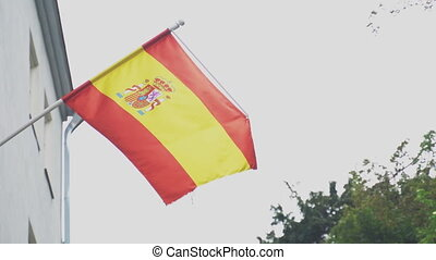 Spanish flag on a flagpole waving on house.