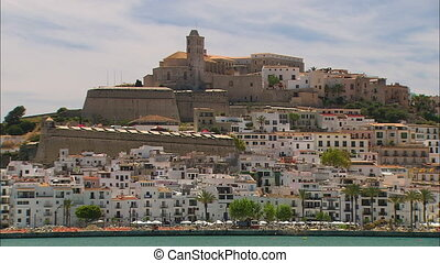 Low-angle still shot of an island hill with crowded white apartment blocks, and an ancient and historical building at the hilltop with long wind towers, island scene, Ibiza Island, Spain