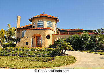 Spanish home with thick stucco and rounded edges. Enclosed patio and entryway supports a hint of Pueblo or Pueblo Deco style. Tiled roof, arched windows and lush tropical landscaping completes this beautiful theme.
