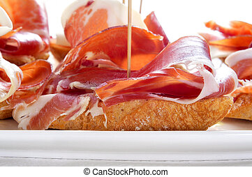 spanish pinchos de jamon, serrano ham served on bread