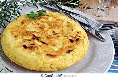 Spanish Potato omelette decorated with branches of rosemary served on a plate