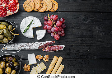 Spanish snacks, meat cheese, herbs, on black wooden table, top view with copy space for text