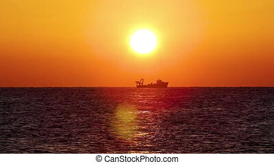 Spanish sunrise over the ocean with fisher boat
