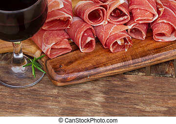 spanish tapas - slices of cured pork ham jamon with red wine...
