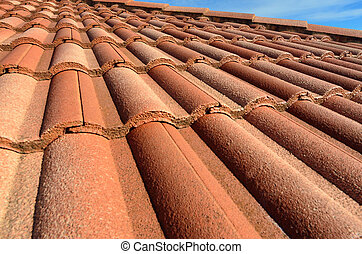 Spanish style ceramic tile roof with blue sky and whit clouds sunny day. Background texture