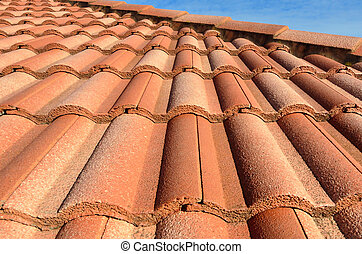 Spanish style ceramic tile roof with blue sky. Background texture
