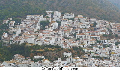 Spanish white village of Andalusia surrounded by mountains and trees.