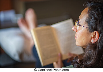 Spanish woman at home with a book