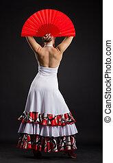 Spanish woman dancing flamenco against dark background -...