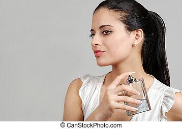 spanish woman spraying perfume on grey background