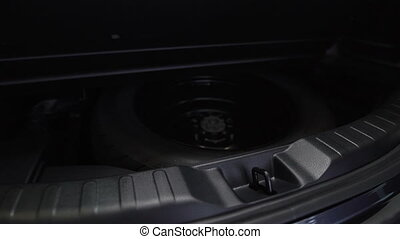 Spare tire in the trunk of a modern car. In showroom