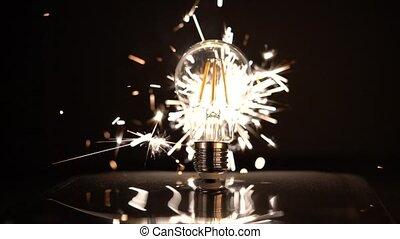 Sparkler Behind LED Light Bulb Slow Motion With Sparks Out of Focus.