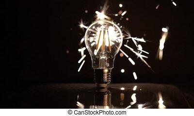 Sparkler Behind LED Light Bulb With Out of Focus Sparks.