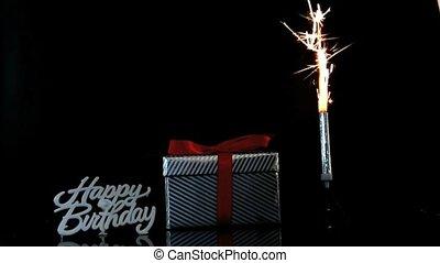 Sparkler burning beside gift and ha