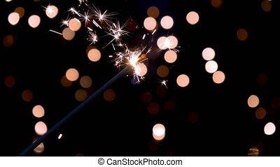 Sparkler burning in front of ambient lights. Gun powder...