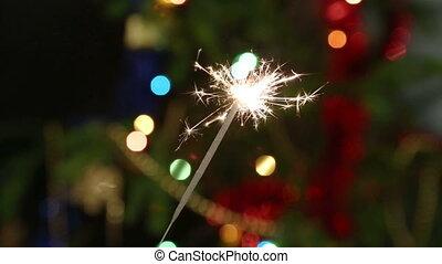 sparkler burning on background decorated Christmas tree