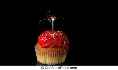Sparkler burning on red birthday cupcake in slow motion
