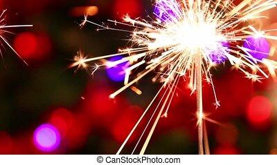 Sparkler - Burning sparkler with colorful background