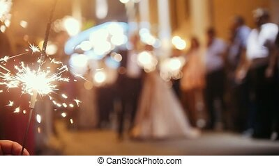 Sparkler in hands on a wedding - bride, groom and guests holding lights in, defocused and slow-motion