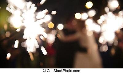 Sparkler in hands on a wedding - bride, groom and guests holding lights in, defocused