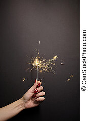 Sparkler in woman hand with red nail polish
