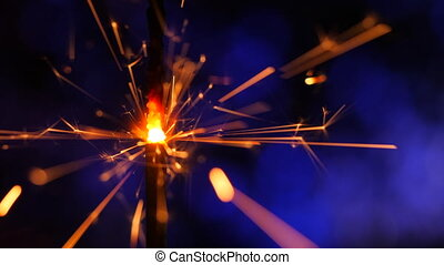 Sparkler Over Blue. Gun powder sparks shot against deep dark background. Burning fuse or bengal fire Isolated. Mojo-style coloring. Lightening Christmas sparkler