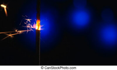 Sparkler Over Blue. Gun powder sparks shot against deep dark background. Burning fuse or bengal fire Isolated. Mojo-style coloring. Lightening Christmas sparkler.
