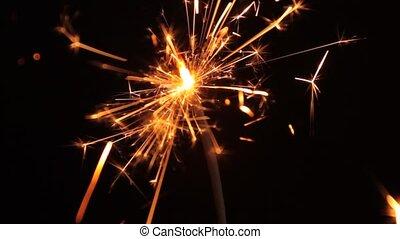 Sparkler - Burning sparkler on a black background