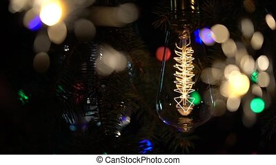Sparklers and a light bulb are lit against the backdrop of a Christmas tree . Close up . Slow motion