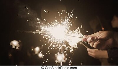 Sparklers burn at night, bright light.