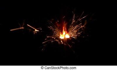 Sparklers burning on a black background. Slow motion -...