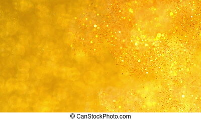 Sparkles in water. Gold glitter reacting in water creating...