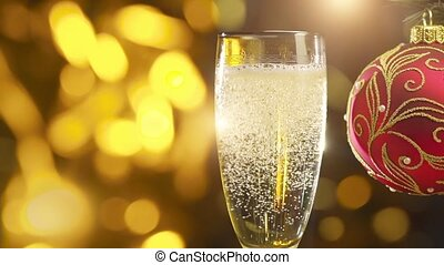 sparkling champagne in glasse and red decoration ball -...