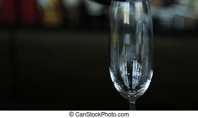 Sparkling champagne is filling crystal wine glass that...