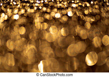 Sparkling light boke blur. Gold glitter particles background.